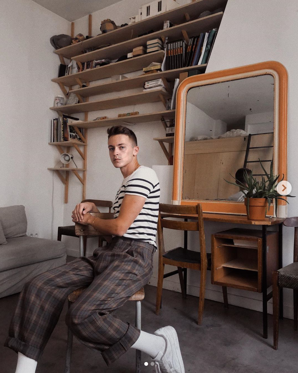 guy sitting on a stool in front of a desk with a mirror and a wall of shelves
