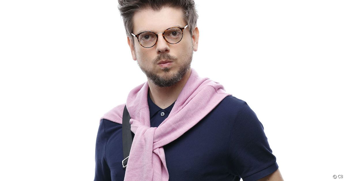 close up of a man with glasses with a pink sweater tied around his shoulders